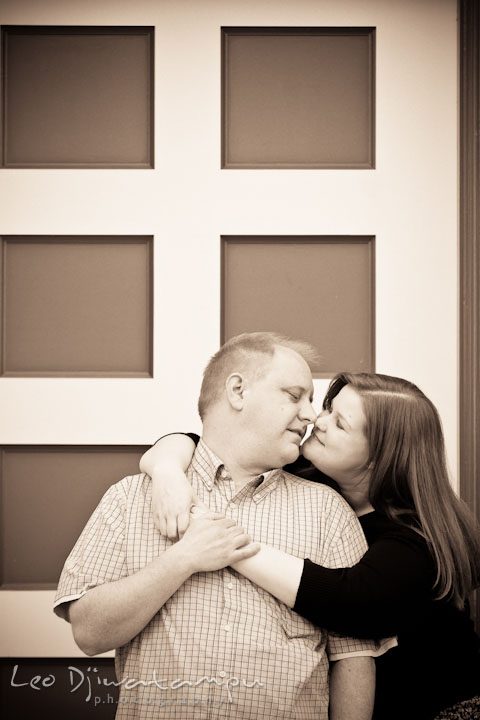Engaged couple cuddling by an antique door. Pre wedding engagement photo session at Glen Echo Park Maryland by wedding photographer Leo Dj Photography