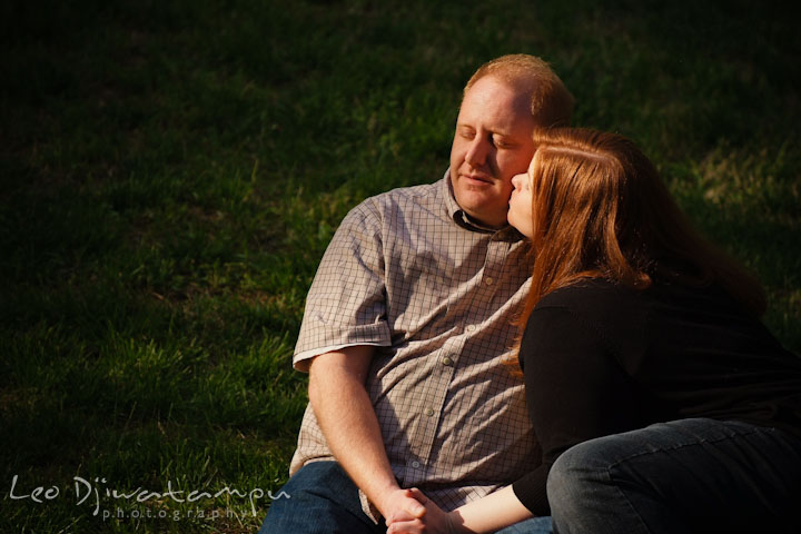 Engaged girl sitting on the ground with her fiancé and kissed him. Pre wedding engagement photo session at Glen Echo Park Maryland by wedding photographer Leo Dj Photography