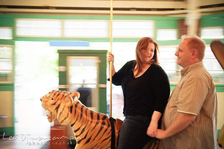Engaged couple having fun riding the tiger on the carousel. Pre wedding engagement photo session at Glen Echo Park Maryland by wedding photographer Leo Dj Photography