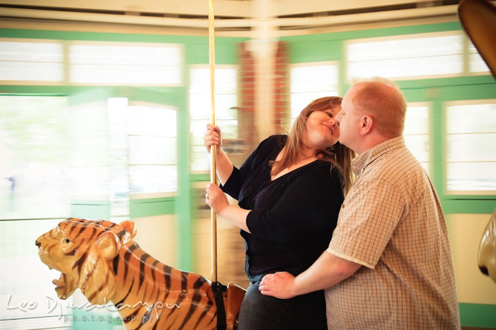 Engaged girl on carousel trying to kiss her fiancé. Pre wedding engagement photo session at Glen Echo Park Maryland by wedding photographer Leo Dj Photography
