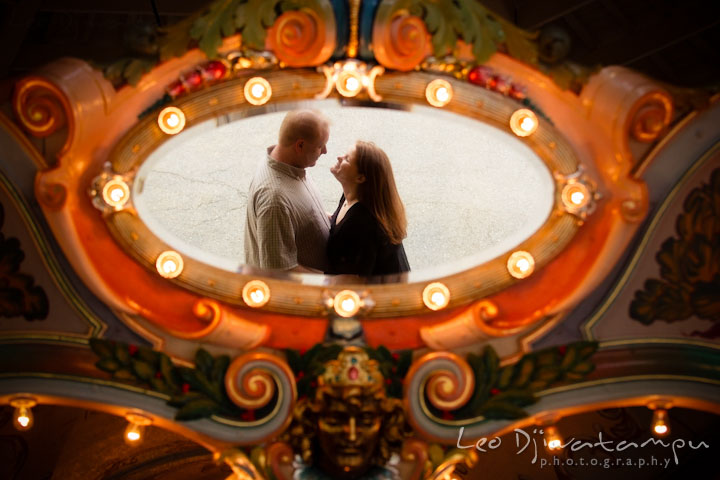 Engaged couple hugging, reflected on a carousel mirror. Pre wedding engagement photo session at Glen Echo Park Maryland by wedding photographer Leo Dj Photography