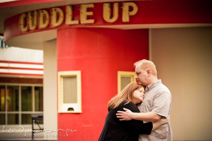 Engaged guy hugging his fiancée by the cuddle up sign. Pre wedding engagement photo session at Glen Echo Park Maryland by wedding photographer Leo Dj Photography