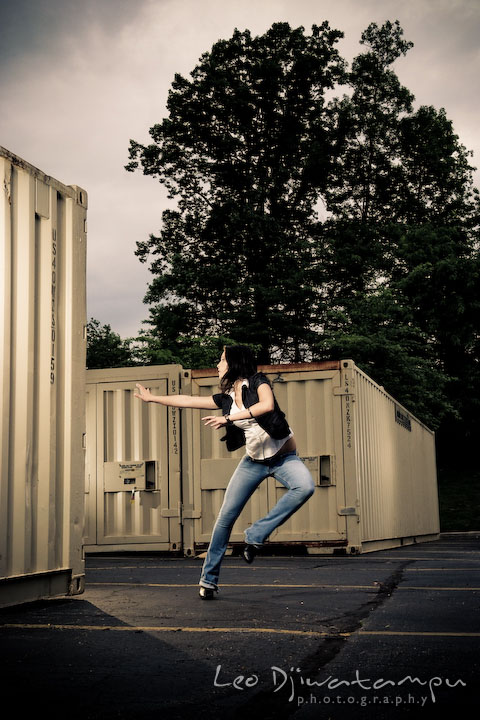 Girl model running away from something by storage containers. Lighting Essentials Workshops - Baltimore with Don Giannatti