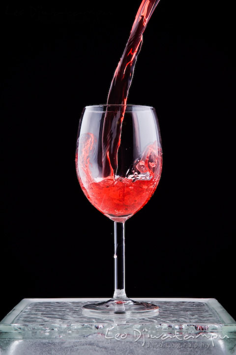 Pouring wine into a wine glass with some splash inside. Lighting Essentials Workshops - Baltimore with Don Giannatti