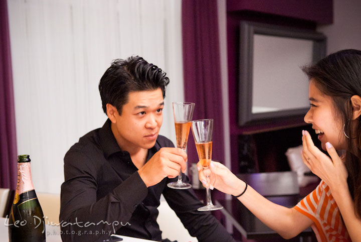 A guy and a girl toast champagne before the proposal. Engagement proposal and pre wedding photo session at Restaurant Michel at Ritz-Carlton Hotel, Tysons Corner, Virginia, by Leo Dj Photography