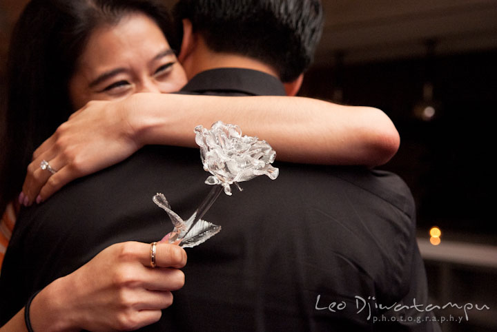 Engaged girl hugged her fiancé while holding the crystal rose stem. Engagement proposal and pre wedding photo session at Restaurant Michel at Ritz-Carlton Hotel, Tysons Corner, Virginia, by Leo Dj Photography