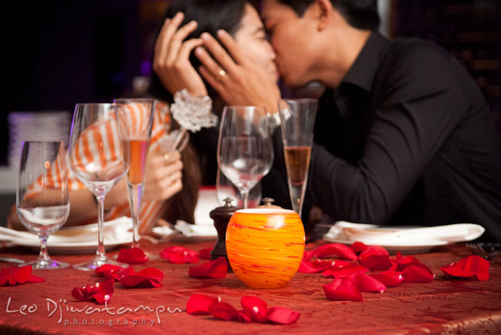 Engaged couple kissing at their dining table. Engagement proposal and pre wedding photo session at Restaurant Michel at Ritz-Carlton Hotel, Tysons Corner, Virginia, by Leo Dj Photography