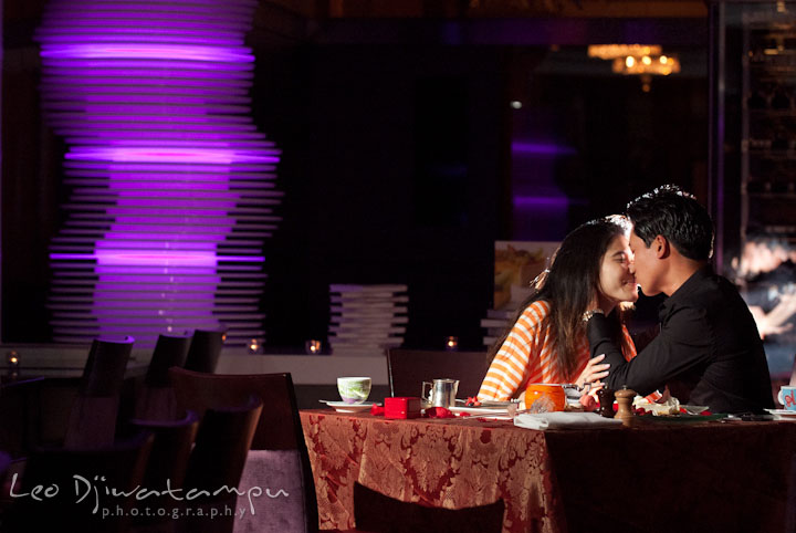 A guy and his fiancée kissing by the dinner table. Engagement proposal and pre wedding photo session at Restaurant Michel at Ritz-Carlton Hotel, Tysons Corner, Virginia, by Leo Dj Photography