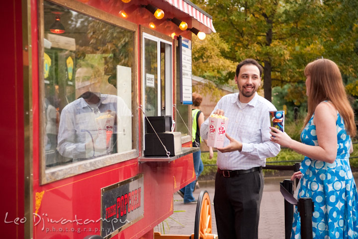 Engaged couple ordering pop-corn and soda drink at the stand. Washington DC National Zoo pre-wedding engagement session by Leo Dj Photography