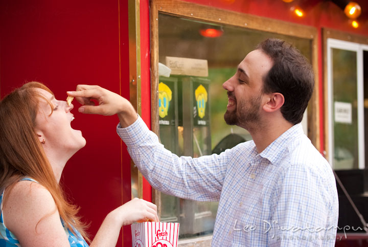 Engaged guy teasing his fiancée with a pop-corn. Washington DC National Zoo pre-wedding engagement session by Leo Dj Photography