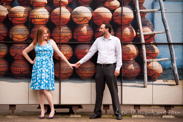 Engaged guy holding his fiancée's hand by a mural of African pottery. Washington DC National Zoo pre-wedding engagement session by Leo Dj Photography