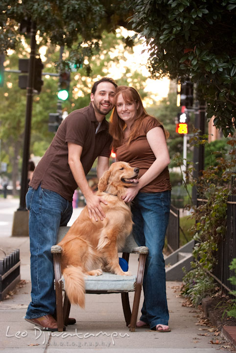 Engaged guy and girl posing with their dog on the curb. Dupont Circle Washington DC pre-wedding engagement session by Leo Dj Photography