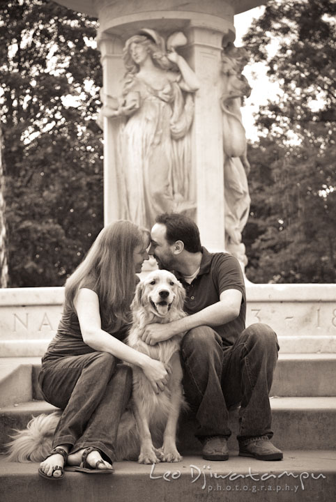 Engaged guy cuddling with his fiancée, with their dog in the middle. Dupont Circle Washington DC pre-wedding engagement session by Leo Dj Photography