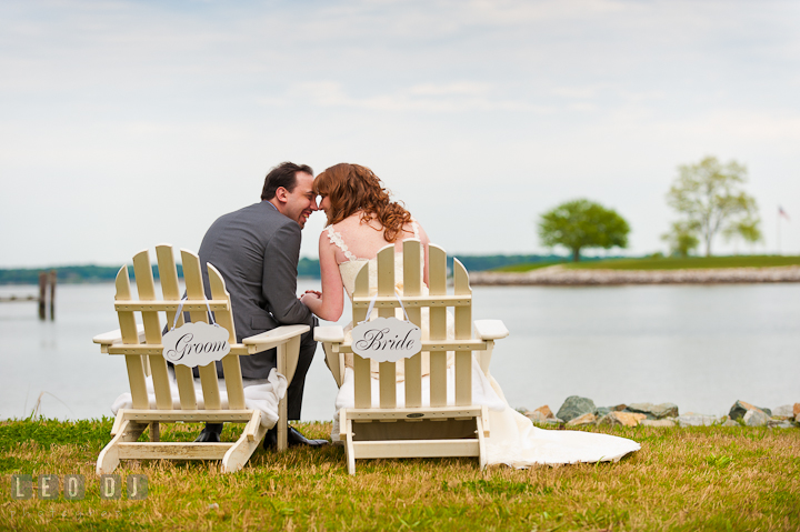 Bride and Groom sitting on adirondack chairs cuddling, overlooking at the water. Harbourtowne Golf Resort wedding photos at St. Michaels, Eastern Shore, Maryland by photographers of Leo Dj Photography.