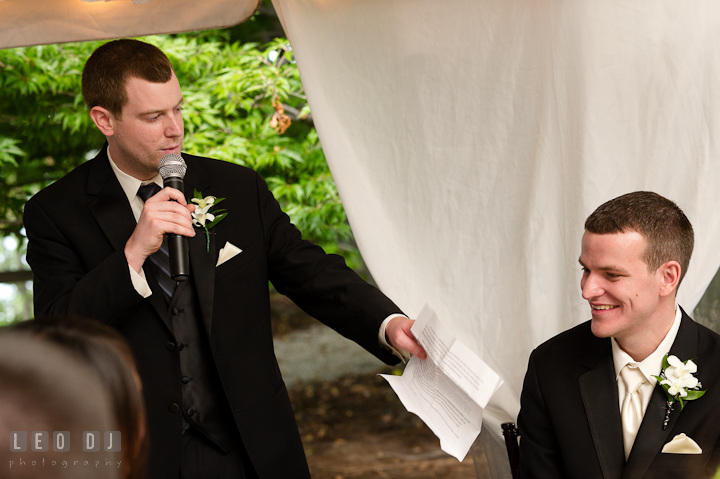 Groom smiling listening to Best Man's speech. Historic London Town and Gardens wedding photos at Edgewater Annapolis, Maryland by photographers of Leo Dj Photography. http://leodjphoto.com