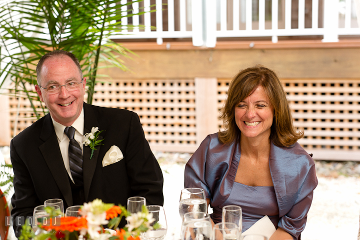 Father and Mother of Bride laughing listening to Best Man's speech. Historic London Town and Gardens wedding photos at Edgewater Annapolis, Maryland by photographers of Leo Dj Photography. http://leodjphoto.com