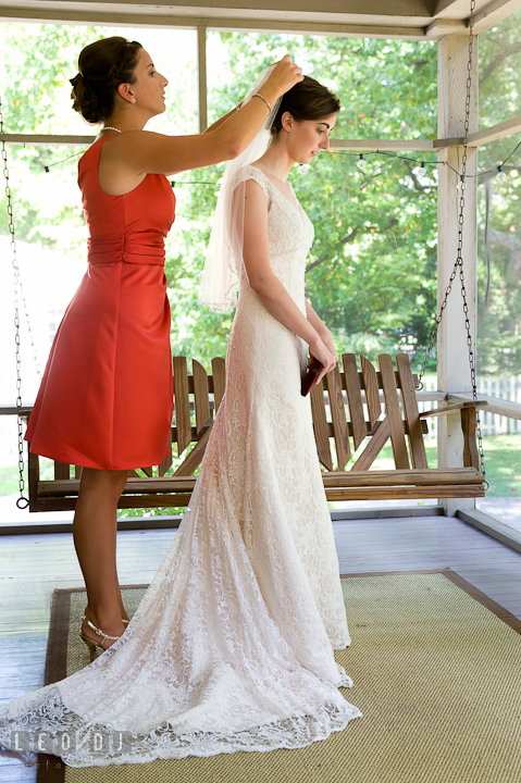 Matron of honor putting on veil on Bride. Saint John the Evangelist church wedding ceremony photos at Severna Park, Maryland by photographers of Leo Dj Photography. http://leodjphoto.com