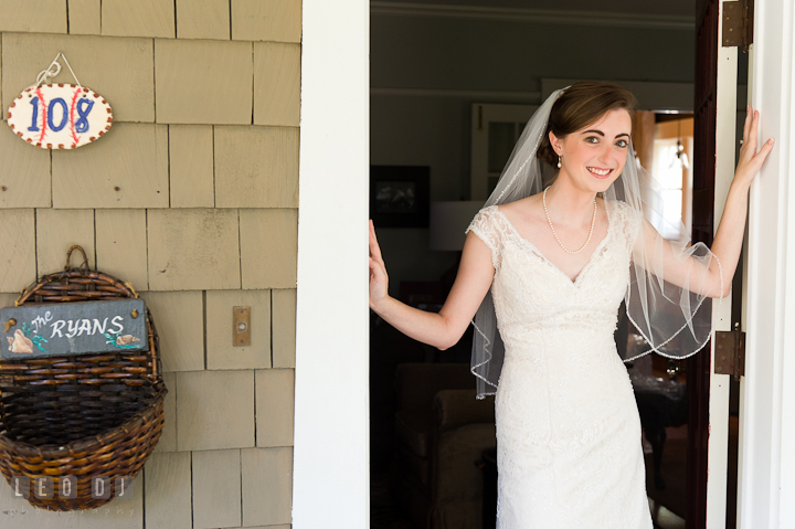 Bride posing and smiling in front of the house door. Saint John the Evangelist church wedding ceremony photos at Severna Park, Maryland by photographers of Leo Dj Photography. http://leodjphoto.com