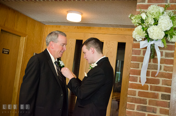 Groom helping his Father put on the boutonniere. Saint John the Evangelist church wedding ceremony photos at Severna Park, Maryland by photographers of Leo Dj Photography. http://leodjphoto.com