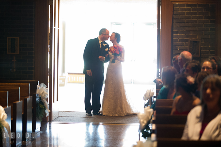 Father of Bride kissed daughter before escorting her down the isle. Saint John the Evangelist church wedding ceremony photos at Severna Park, Maryland by photographers of Leo Dj Photography. http://leodjphoto.com