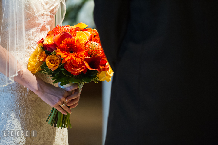Bride holding her beautiful orange floral bouquet. Saint John the Evangelist church wedding ceremony photos at Severna Park, Maryland by photographers of Leo Dj Photography. http://leodjphoto.com