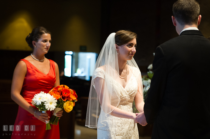 Bride holding Groom's hands and looking at him. Saint John the Evangelist church wedding ceremony photos at Severna Park, Maryland by photographers of Leo Dj Photography. http://leodjphoto.com