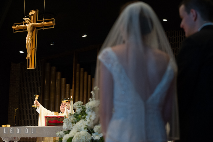 Priest blessing the bread and wine. Saint John the Evangelist church wedding ceremony photos at Severna Park, Maryland by photographers of Leo Dj Photography. http://leodjphoto.com