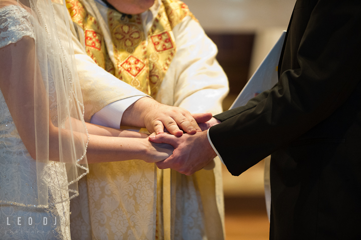 The priest, Father Jim Proffitt, blessing the Bride and Groom. Saint John the Evangelist church wedding ceremony photos at Severna Park, Maryland by photographers of Leo Dj Photography. http://leodjphoto.com