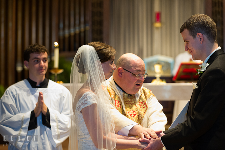 Bride and Groom smiling while blessed by the Priest. Saint John the Evangelist church wedding ceremony photos at Severna Park, Maryland by photographers of Leo Dj Photography. http://leodjphoto.com