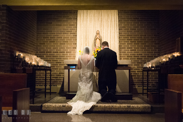 Bride and Groom making a devotion to Mother Mary. Saint John the Evangelist church wedding ceremony photos at Severna Park, Maryland by photographers of Leo Dj Photography. http://leodjphoto.com