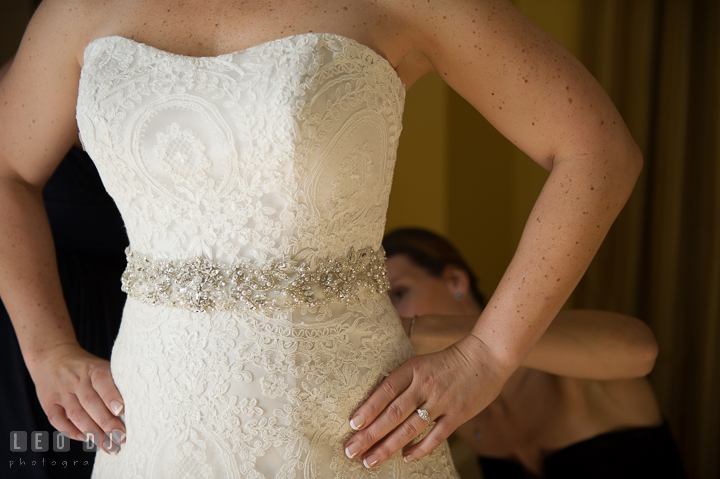 Bridesmaid help putting on Wedding gown on Bride. The Tidewater Inn wedding, Easton, Eastern Shore, Maryland, by wedding photographers of Leo Dj Photography. http://leodjphoto.com