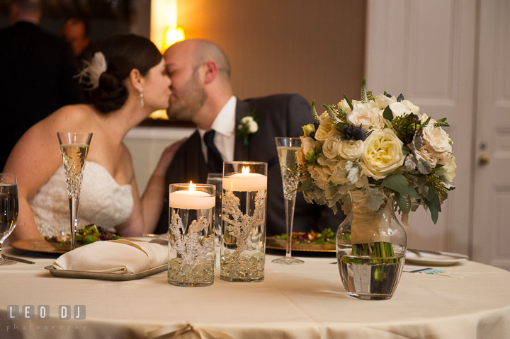 Bride and Groom kissing at sweetheart table behind Bride's floral bouquet by florist Monteray Farms. The Tidewater Inn wedding, Easton, Eastern Shore, Maryland, by wedding photographers of Leo Dj Photography. http://leodjphoto.com