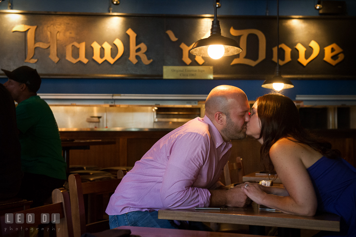 Engaged couple in the Hawk n Dove restaurant by the Capitol Hill kissing. Washington DC pre-wedding engagement photo session, by wedding photographers of Leo Dj Photography. http://leodjphoto.com