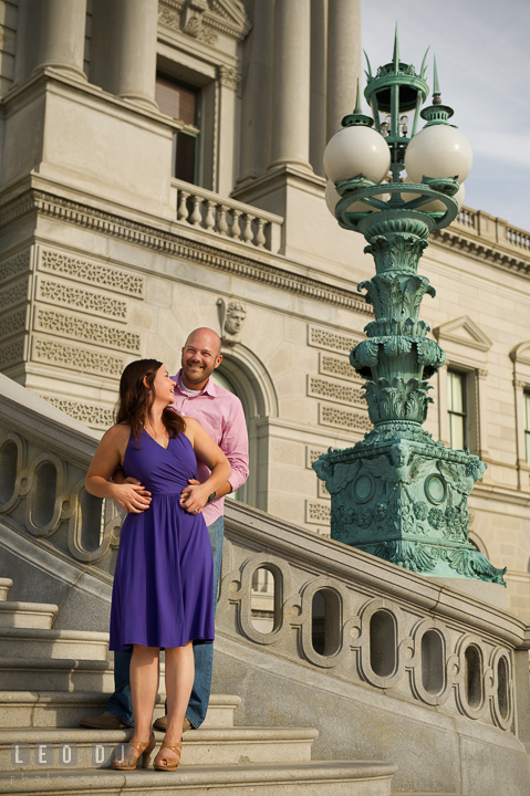 Engaged guy hugging his fiancée by an antique light pole by the Capitol Hill. Washington DC pre-wedding engagement photo session, by wedding photographers of Leo Dj Photography. http://leodjphoto.com