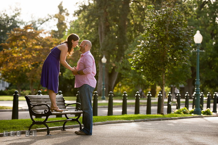 Engaged girl standing on a bench almost kissing her fiancé by the Capitol Hill. Washington DC pre-wedding engagement photo session, by wedding photographers of Leo Dj Photography. http://leodjphoto.com