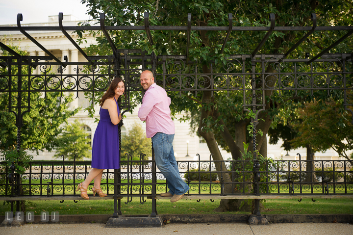 Engaged couple holding on antique bench poles by the Capitol Hill. Washington DC pre-wedding engagement photo session, by wedding photographers of Leo Dj Photography. http://leodjphoto.com
