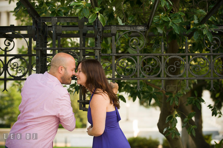 Engaged guy hanging on bench poles and almost kiss his fiancée by the Capitol Hill. Washington DC pre-wedding engagement photo session, by wedding photographers of Leo Dj Photography. http://leodjphoto.com