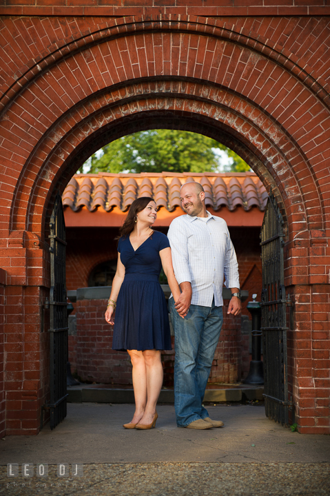 Engaged guy holding hands with his fiancée under a brick archway by the Capitol Hill. Washington DC pre-wedding engagement photo session, by wedding photographers of Leo Dj Photography. http://leodjphoto.com