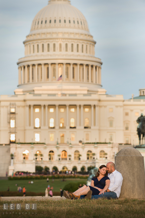 Engaged couple sitting on the ground and cuddling in front of the Capitol Hill. Washington DC pre-wedding engagement photo session, by wedding photographers of Leo Dj Photography. http://leodjphoto.com