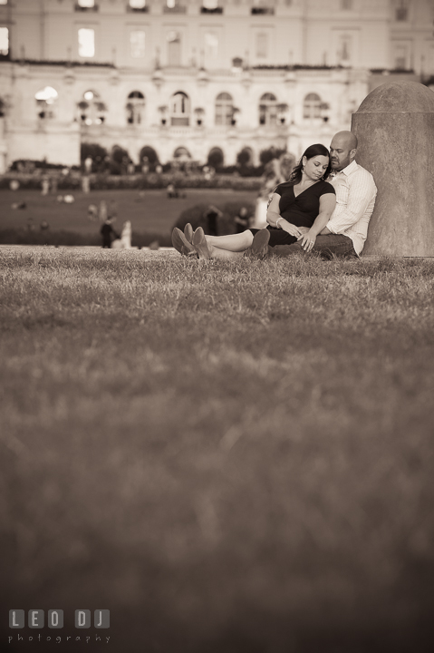 Engaged girl sitting on the lawn leaning against her fiancé by the Capitol Hill. Washington DC pre-wedding engagement photo session, by wedding photographers of Leo Dj Photography. http://leodjphoto.com