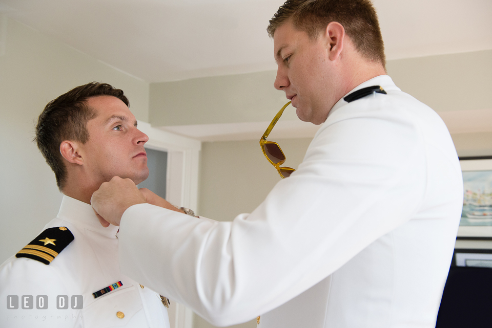Groom helping his groomsman, a Naval officer, fixing his uniform collar. USNA, US Naval Academy military wedding at Annapolis Maryland, by wedding photographers of Leo Dj Photography. http://leodjphoto.com
