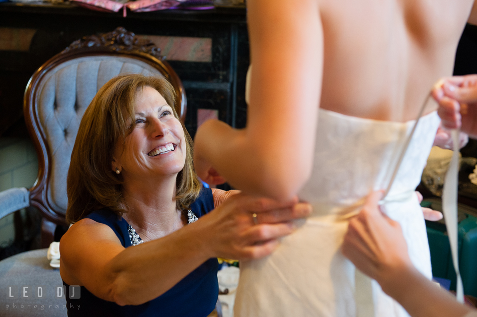 Mother of Bride laughing while helping Bride wearing her wedding gown. USNA, US Naval Academy military wedding at Annapolis Maryland, by wedding photographers of Leo Dj Photography. http://leodjphoto.com