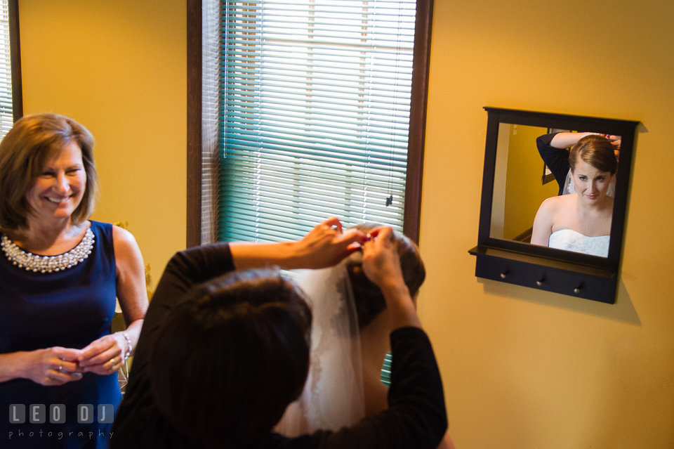 Bride looking at mirror while having her veil put on. Mom smiling. USNA, US Naval Academy military wedding at Annapolis Maryland, by wedding photographers of Leo Dj Photography. http://leodjphoto.com