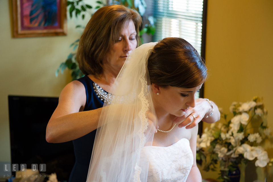 Mother of the Bride helping her daughter put on pearl necklace from Grandmother. USNA, US Naval Academy military wedding at Annapolis Maryland, by wedding photographers of Leo Dj Photography. http://leodjphoto.com