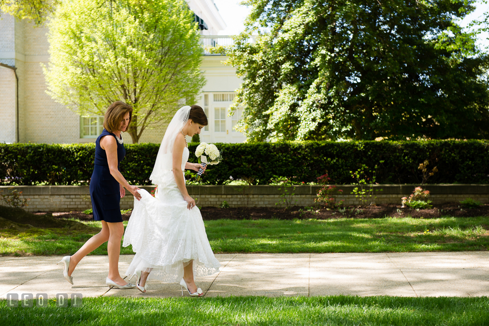 Mother of the Bride holding her daughter's wedding gown train as she walks to the Chapel. USNA, US Naval Academy military wedding at Annapolis Maryland, by wedding photographers of Leo Dj Photography. http://leodjphoto.com