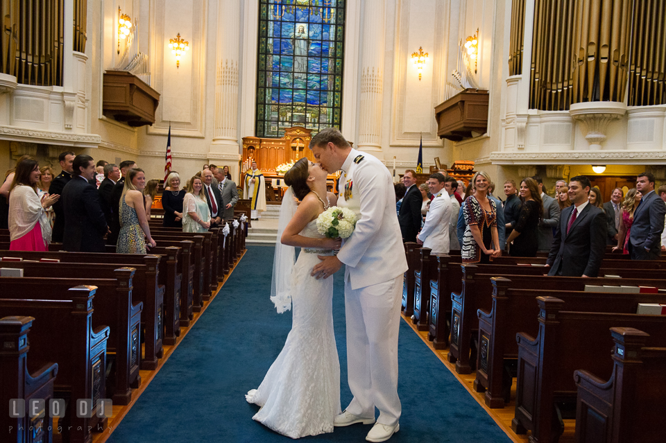 Bride and Groom kissing as they walk out of the aisle during the recessional. USNA, US Naval Academy military wedding at Annapolis Maryland, by wedding photographers of Leo Dj Photography. http://leodjphoto.com