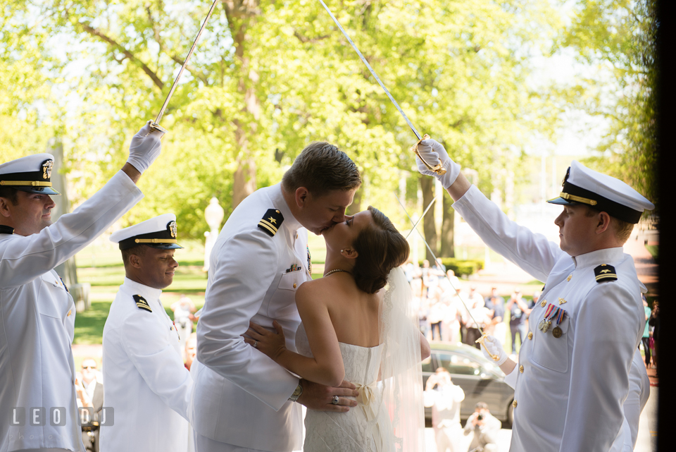 Bride and Groom kissing under the first pair of swordsmen of the arch of swords. USNA, US Naval Academy military wedding at Annapolis Maryland, by wedding photographers of Leo Dj Photography. http://leodjphoto.com