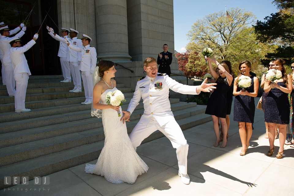 Bride and Groom doing a goofy pose as they pass through the arch of swords after the ceremony. USNA, US Naval Academy military wedding at Annapolis Maryland, by wedding photographers of Leo Dj Photography. http://leodjphoto.com