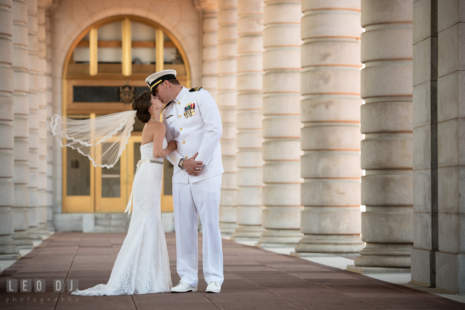 Bride and Naval officer Groom kissing in between the columns. USNA, US Naval Academy military wedding at Annapolis Maryland, by wedding photographers of Leo Dj Photography. http://leodjphoto.com