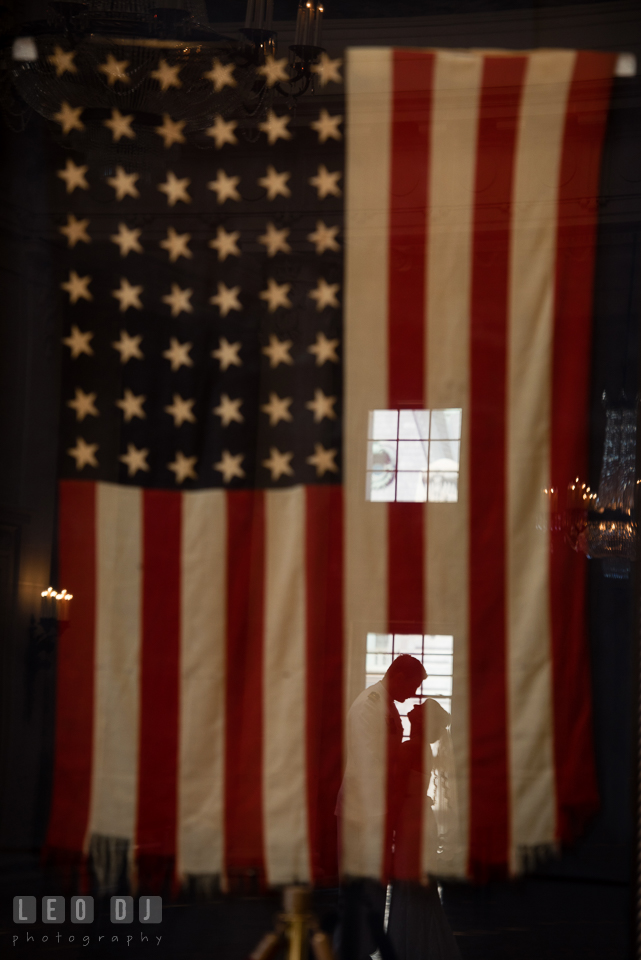 Silhouette of Bride and Groom almost kissing on a historic American flag. USNA, US Naval Academy military wedding at Annapolis Maryland, by wedding photographers of Leo Dj Photography. http://leodjphoto.com